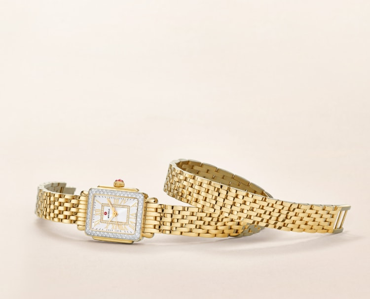 Deco Madison Mini watch in 18k gold features a mother-of-pearl dial with gold Roman numeral indexes, diamond-covered bezel and 18k gold seven-link double-wrap bracelet.