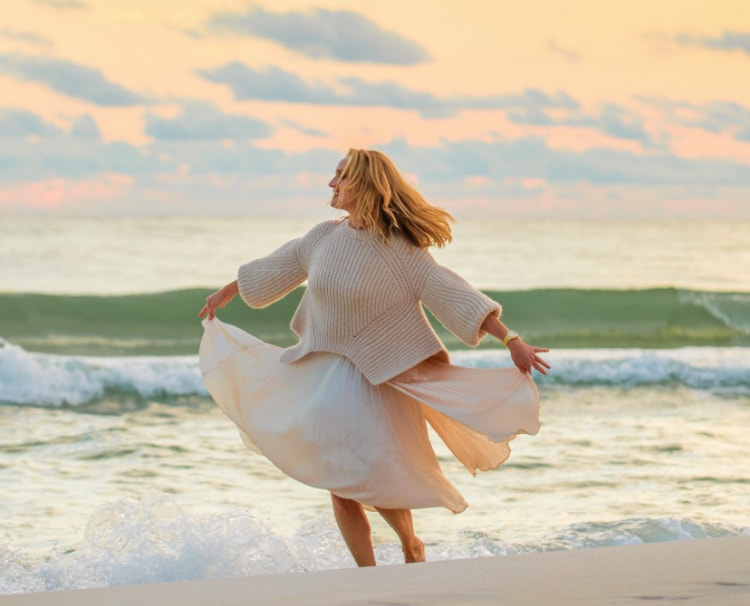 Sophisticated woman twirling along a beach wearing the Deco watch in stainless.