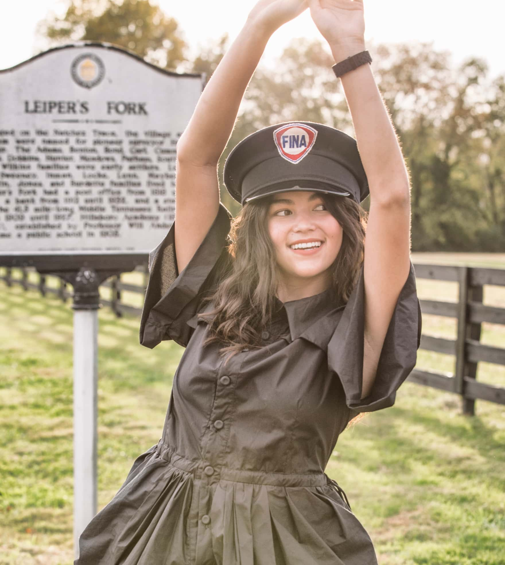 Stylish young woman standing in front of Leiper's Fork, Tennessee sign wearing a black MICHELE watch.