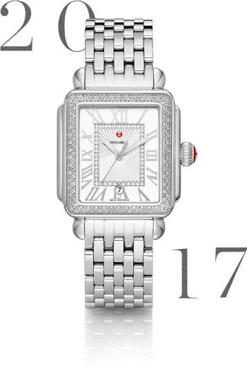 Deco Madison watch featuring silver-tone Roman numeral indexes, diamond innerring, date window, MICHELE logotype atop the dial and signature seven-link bracelet in stainless.