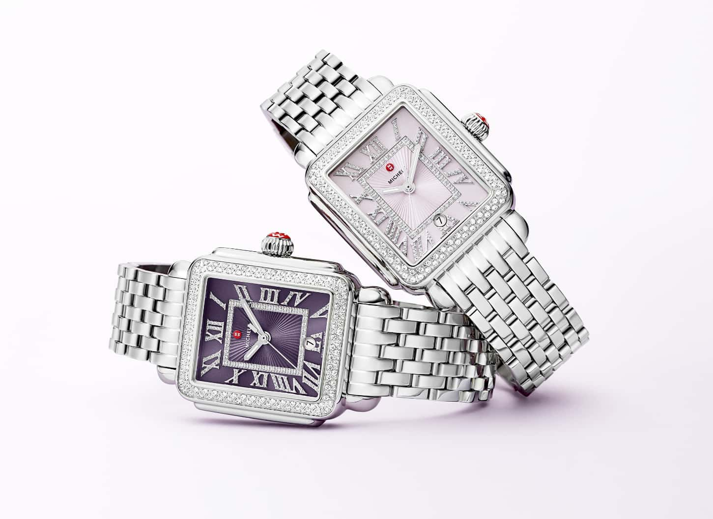 Two Deco Madison watches in stainless featuring lilac and violet dials and diamond-covered Roman numeral indexes.